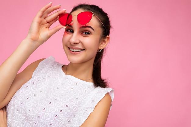 Nahaufnahmeportrait fotoaufnahme einer schönen positiven lächelnden jungen brunettefrau, die legere sommerkleidung und eine stilvolle sonnenbrille trägt, die über der bunten hintergrundwand lokalisiert wird, die kamera betrachtet. freiraum