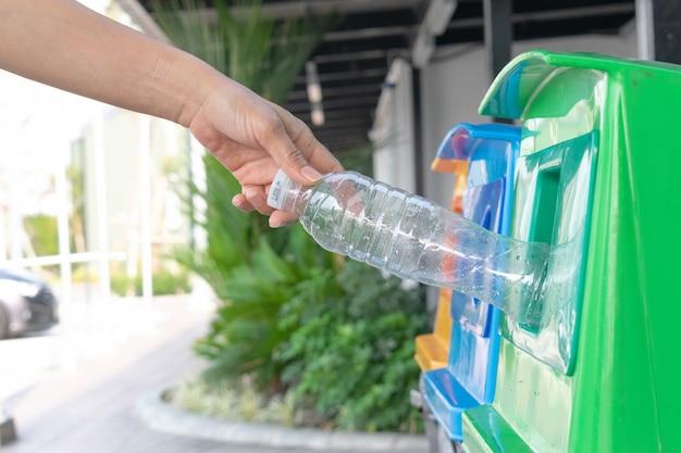 Nahaufnahmeportrait-frauenhand, die leere plastikwasserflasche im wiederverwertungsbehälter wirft.