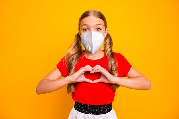 Nahaufnahmeportrait ihr gesundes attraktives mädchen mit sicherheits-atemschutzmaske, das herzform zeigt, stoppt die immunität gegen grippeerkrankungen isoliert heller, lebendiger glanz, lebendiger gelber farbhintergrund