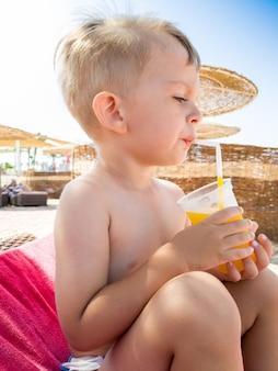 Nahaufnahmeportriat des kleinen kleinkindjungen, der orangensaft am meeresstrand trinkt?