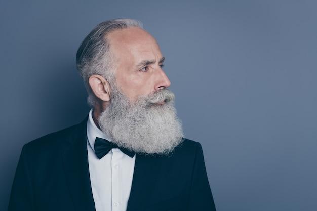 Nahaufnahmeprofil seitenansicht porträt seines er schönen attraktiven inhalts gut gepflegter grauhaariger mann, der smoking trägt, der beiseite lokalisiert über grau violett lila pastellfarbenhintergrund schaut