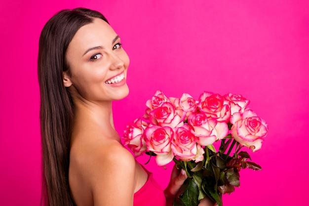 Nahaufnahmeprofil-seitenansichtporträt des netten attraktiven reizenden schönen fröhlichen langhaarigen mädchens, das in händen niedlichen organischen blumenstrauß lokalisiert auf hellem lebendigem glanz lebendigem rosa fuchsiafarbhintergrund hält