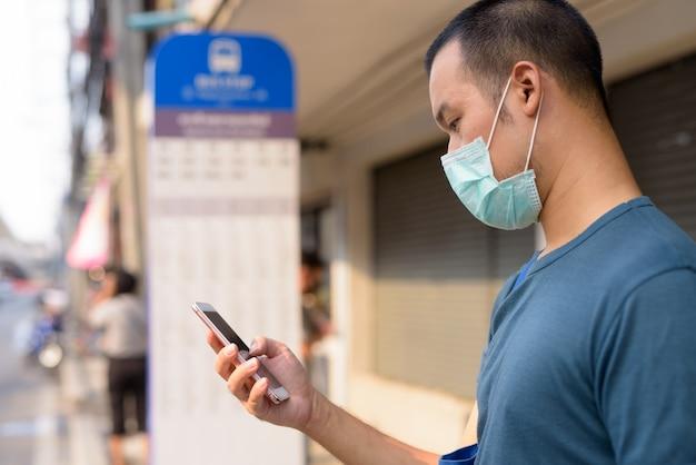 Nahaufnahmeprofilansicht des jungen asiatischen mannes, der telefon mit maske an der bushaltestelle verwendet