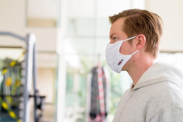 Nahaufnahmeprofilansicht des jungen mannes, der maske im fitnessstudio während der coronavirus-covid-19-pandemie trägt