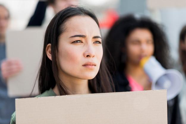Nahaufnahmeprotestierender, der einen karton hält