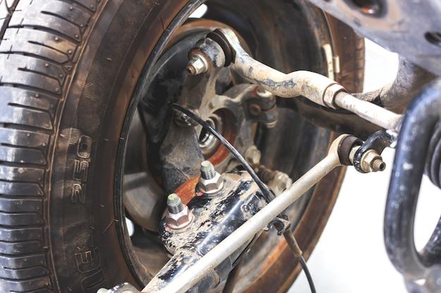 Nahaufnahmeräder und stoßdämpfer mit reparatur der aufhängung am auto.
