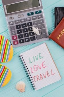 Nahaufnahmerechner und notizblock mit wörtern leben liebesreisen. flache zusammensetzung der reise.