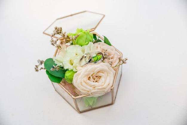 Nahaufnahmeringe von braut und bräutigam liegen auf einem kissen aus lebenden rosenknospen in einer glasbox auf einem weißen tisch