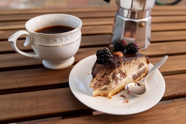 Nahaufnahmescheibe des kuchens mit kaffeetasse