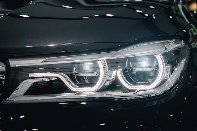 Nahaufnahmescheinwerfer des modernen autos während schalten licht in der nacht ein.