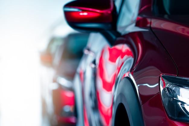Nahaufnahmescheinwerfer des roten autos, das im modernen ausstellungsraum geparkt wird. neues und luxuriöses auto. autohauskonzept. automobilindustrie. autoleasing. vorderansicht des roten glänzenden autos, das in einer reihe im ausstellungsraum geparkt wird.