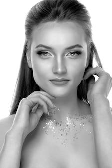 Nahaufnahmeschönheitsaufnahme mit attraktivem blondem modell, das mit professionellem make-up und funkeln auf ihrem hals aufwirft. schwarzweißbild