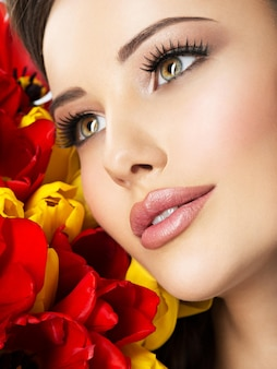 Nahaufnahmeschönheitsgesicht der jungen frau mit blumen. attraktives modell mit roten und gelben tulpen