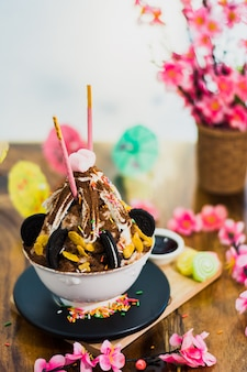 Nahaufnahmeschokolade bingsu auf behälter, bingsu oder bingsoo, koreanischer rasierter eisnachtisch mit süßen belägen a