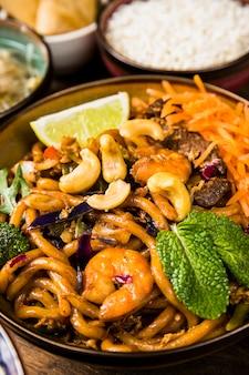 Nahaufnahmeschüssel udon-nudeln mit nüssen; zitronenscheibe; minze und rindfleisch