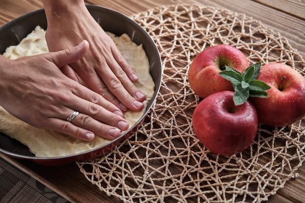 Nahaufnahmeschuss der weiblichen hände, die roten apfelkuchen vorbereiten