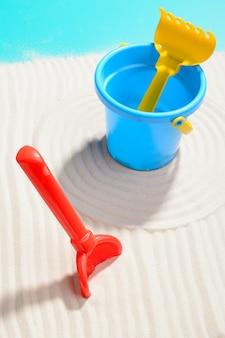 Nahaufnahmeschuss des blauen eimers mit schaufel und rechen auf sand
