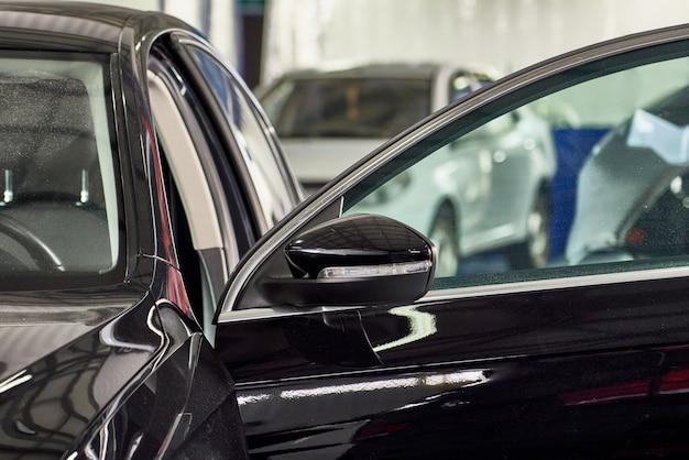 Nahaufnahmeschuss des seitenspiegels des schwarzen modernen autos in der autowerkstatt