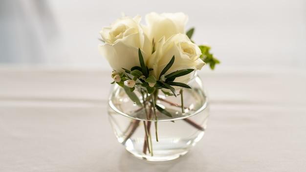 Nahaufnahmeschuss des weißen rosenstraußes in der glasschale lokalisiert