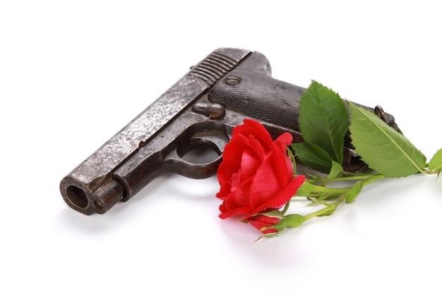 Nahaufnahmeschuss einer waffe und einer roten rose lokalisiert auf einem weißen hintergrund