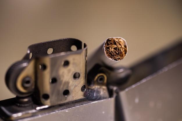 Nahaufnahmeschuss einer zigarette in einem zippofeuerzeug