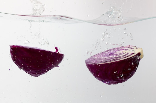 Nahaufnahmeschuss von frisch geschnittenen zwiebelteilen im wasser auf weißem hintergrund