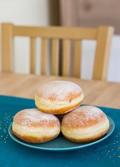 Nahaufnahmeschuss von frischen süßen donuts auf einem blauen teller
