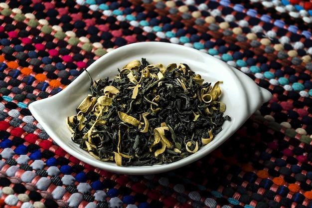 Nahaufnahmeschuss von grünem tee mit orangenblüte in einem weißen teller auf einer bunten tischdecke