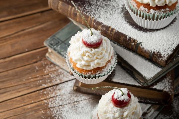 Nahaufnahmeschuss von köstlichen cupcakes mit sahne, puderzucker und einer kirsche oben auf büchern
