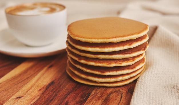Nahaufnahmeschuss von köstlichen pfannkuchen mit einer tasse kaffee