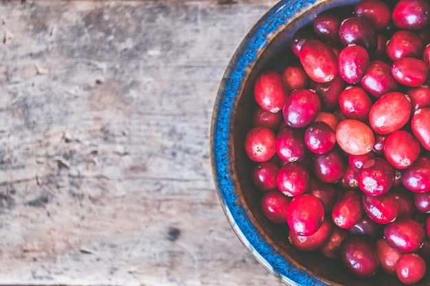 Nahaufnahmeschuss von roten kaffeebohnen auf einer hölzernen grauen oberfläche