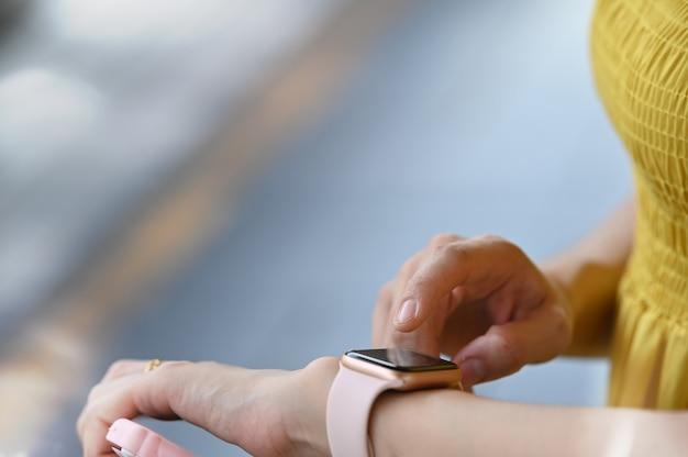 Nahaufnahmeschussfrau, die smartwatch verwendet.