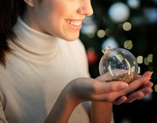Nahaufnahmesmileyfrau, die kugel für weihnachtsbaum hält