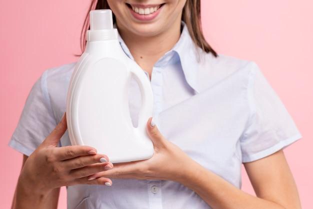 Nahaufnahmesmileyfrau, die reinigungsmittelflasche hält