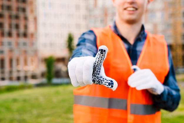 Nahaufnahmesmileymann mit handschuhen und sicherheitsweste