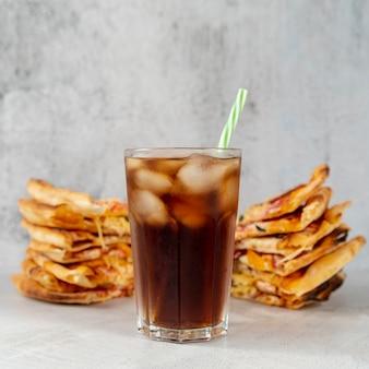 Nahaufnahmesoda-glas mit pizzascheiben