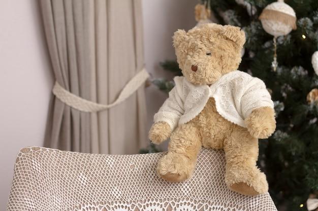 Nahaufnahmespielzeug teddybär betreffen die rückseite eines stuhls mit einer handgemachten gestrickten verpackung auf einem unscharfen hintergrund eines verzierten weihnachtsbaums.