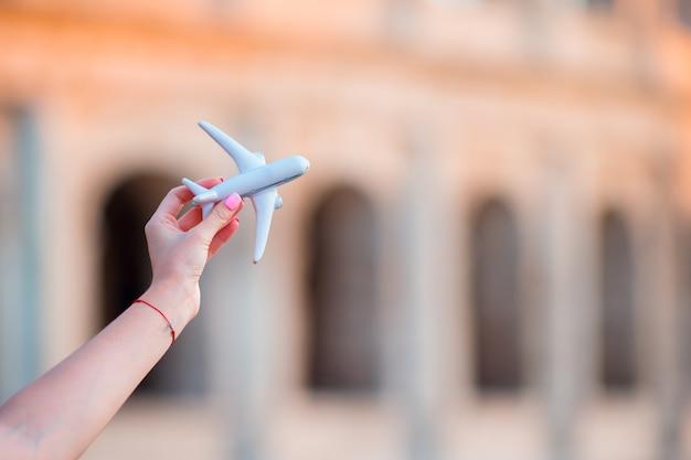 Nahaufnahmespielzeugflugzeug auf colosseum-hintergrund. italienische europäische ferien in rom. konzept der phantasie.