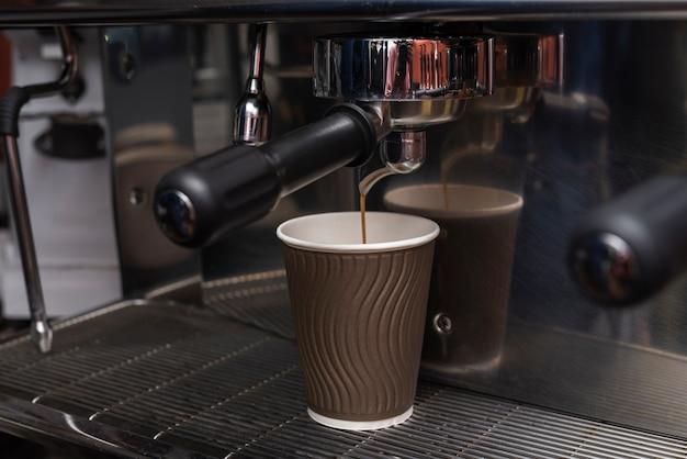 Nahaufnahmespresso, der in kaffeetasse gießt