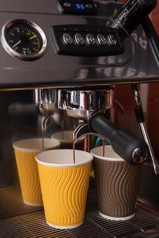 Nahaufnahmespresso, der in kaffeetassen gießt
