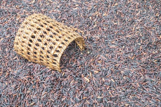Nahaufnahmestapel des schwarzen reises nannte riceberry reis mit hölzerner korbwaren