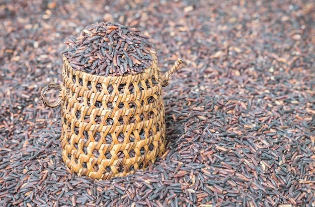 Nahaufnahmestapel des schwarzen reises rief riceberry reis mit hölzerner korbwaren an