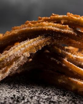 Nahaufnahmestapel von gebratenen churros und von zucker