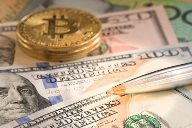 Nahaufnahmestift auf usd-dollar und -bitcoin für geschäftskonzept