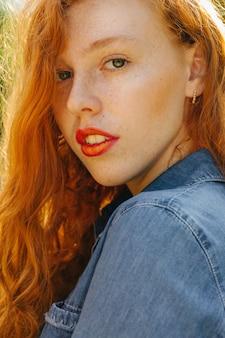 Nahaufnahmestraßenporträt der hübschen rothaarigen jungen frau, die in der sonne aufwirft