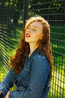 Nahaufnahmestraßenporträt der schönen rothaarigen jungen frau, die in der sonne aufwirft