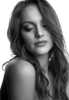 Nahaufnahmestudioporträt einer hübschen frau mit dem lockigen haar und natürlichem make-up. schwarz-weiß-aufnahme