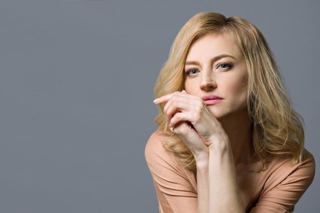 Nahaufnahmestudioportrait der mittleren gealterten blonden frau