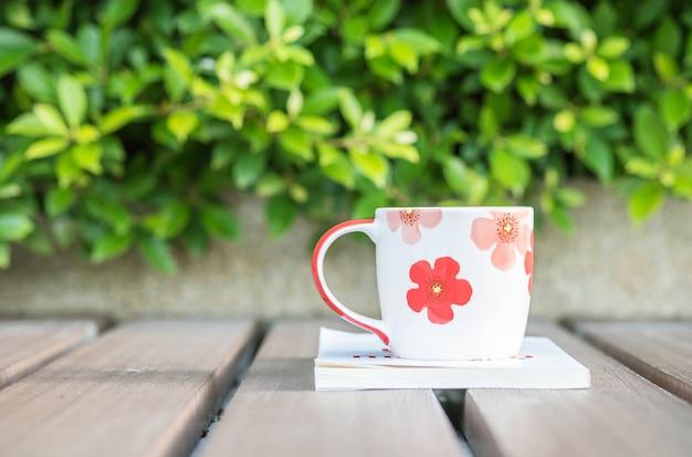 Nahaufnahmetasse kaffee auf weißbuch auf tabelle im gartenhintergrund