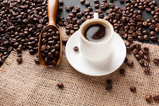 Nahaufnahmetasse kaffee mit bohnen